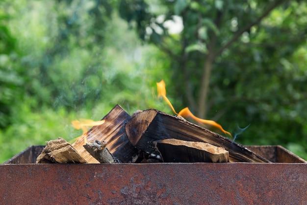 Räuchern von brennholz im grill. picknick in der natur. nahansicht. vorderansicht.