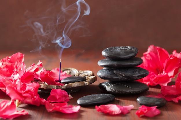 Räucherstäbchen für aromatherapie spa azalee blumen schwarze massagesteine
