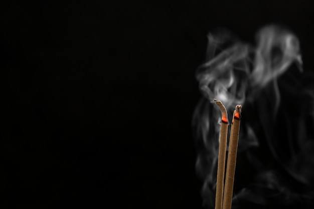 Räucherstäbchen und räucherstäbchenrauche auf schwarzem hintergrund
