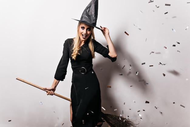 Raffinierte blonde frau, die im hexenkostüm posiert. hübsches kaukasisches mädchen, das spaß an der halloween-party hat.