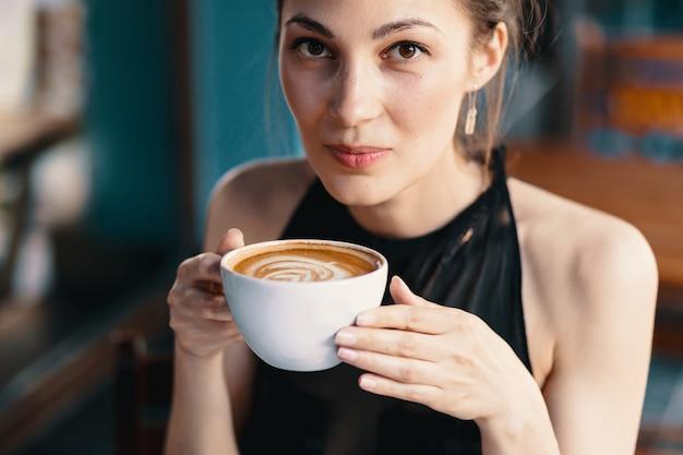 Raffinierte frau, die cappuccino oder latte auf einem vibrierenden, colorfu genießt