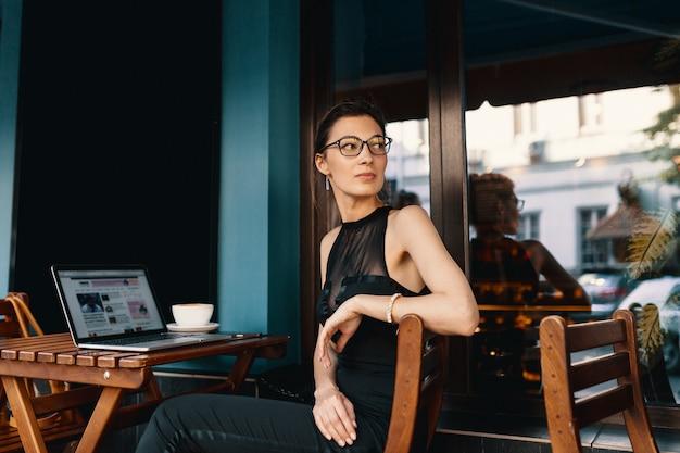 Raffinierte geschäftsfrau in den gläsern, bei tisch sitzend in der caféarbeit