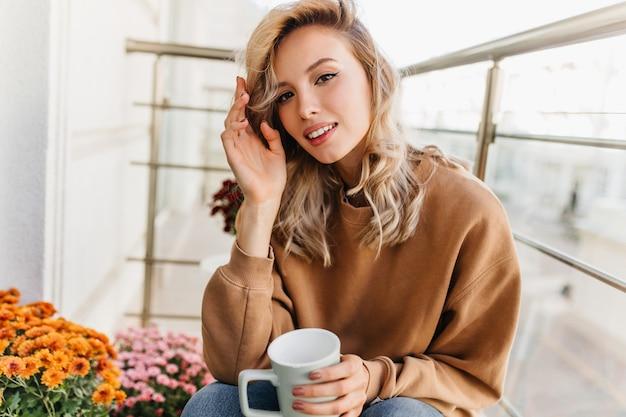 Raffinierte junge frau, die tee am balkon trinkt. hübsches blondes mädchen, das kaffee am morgen genießt.