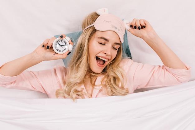 Raffinierte junge frau in der rosa schlafmaske, die mit uhr aufwirft