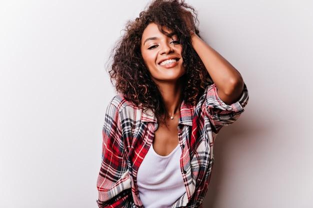 Raffinierte schwarze frau, die ihr lockiges haar auf weiß berührt. lachendes wunderschönes mädchen im roten hemd, das schießen genießt.