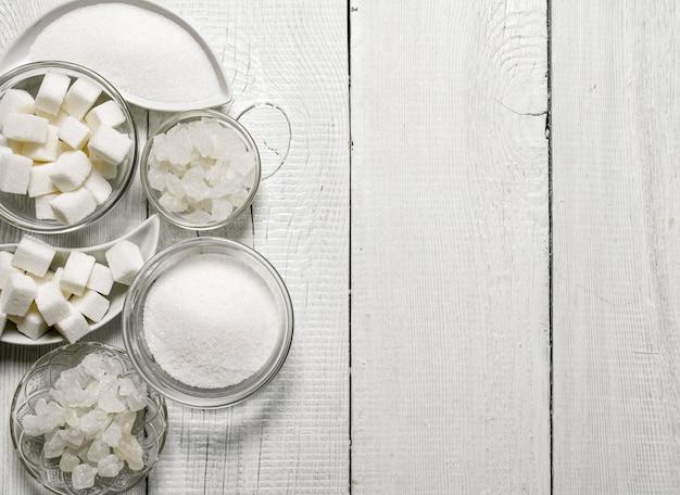 Raffinierter zucker, sand und kristall auf weißem holztisch.