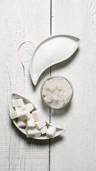 Raffinierter zucker, sand und kristallin. auf weißem holztisch.