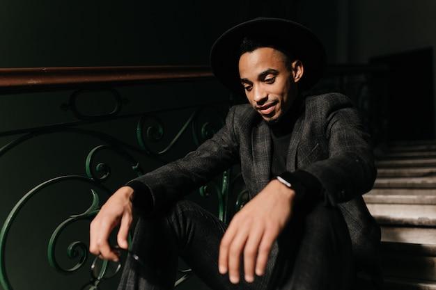 Raffiniertes junges männliches modell, das auf stufen aufwirft. innenfoto des nachdenklichen gut gekleideten schwarzen kerls, der unten schaut.