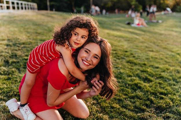 Raffiniertes kleines mädchen, das schwester auf natur umarmt glückliches weibliches modell mit braunen haaren, die mit lockigem kind im park spielen.