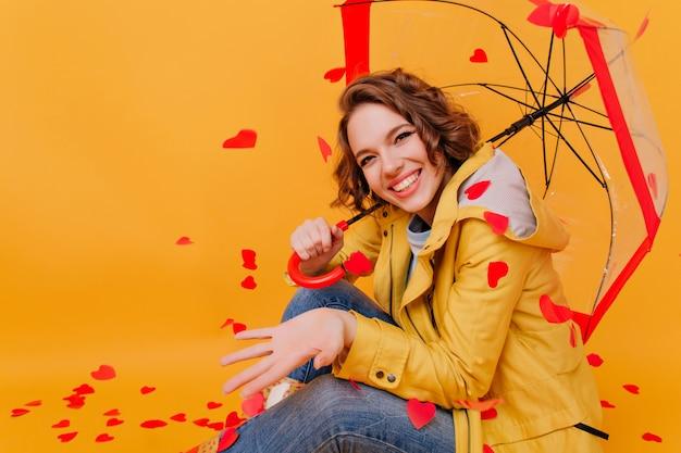 Raffiniertes lachendes mädchen in der trendigen gelben jacke, die unter sonnenschirm aufwirft. studioporträt der anmutigen frau in der guten stimmung, die auf dem boden mit herzen an der wand sitzt.