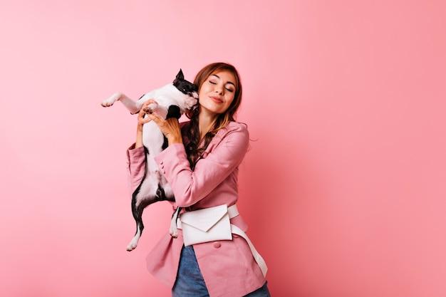 Raffiniertes mädchen, das mit geschlossenen augen lächelt, während es mit niedlichem hund aufwirft. innenporträt der ingwerdame, die spaß mit französischer bulldogge hat.