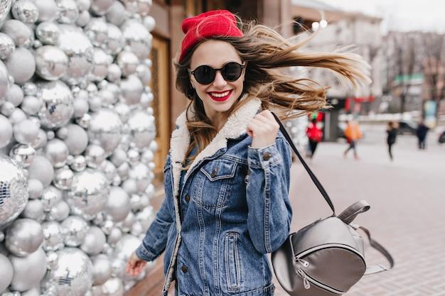 Raffiniertes mädchen in jeansjacke posiert mit trendigem rucksack an der straßenwand. spektakuläre frau im roten hut, die frühlingsmorgen draußen verbringt.