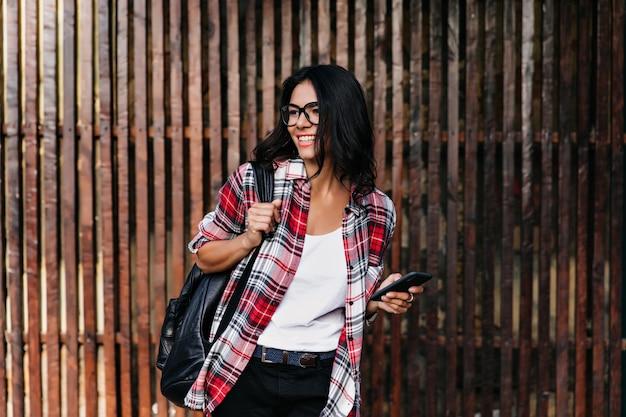 Raffiniertes schwarzhaariges mädchen im karierten hemd, das auf holzwand aufwirft. foto im freien von jocund lateinischem weiblichem modell mit rucksack.