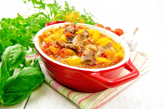 Ragout aus putenfleisch, tomaten, gelber paprika und zwiebeln mit sauce in einem roten kohlenbecken auf einem handtuch auf dem hintergrund eines holzbretts