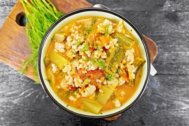 Ragout aus zucchini, hackfleisch und tomaten mit kräutern in einer schüssel auf holzbretthintergrund von oben