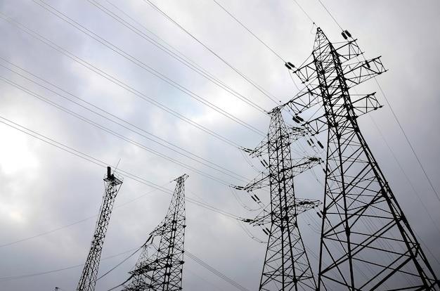 Ragt stromleitungen gegen einen hintergrund des bewölkten himmels hoch. stromübertragungsmasten