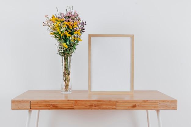 Rahmen auf dem tisch in der nähe von blumen