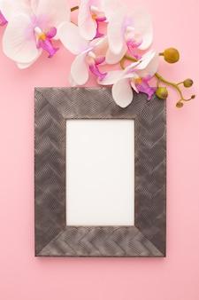 Rahmen auf rosa hintergrund mit orchidee mit platz für text. foto in hoher qualität