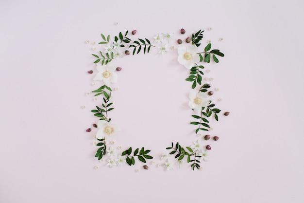 Rahmen aus blumen, zweigen, blättern und blütenblättern mit platz für text auf rosa hintergrund. flach legen