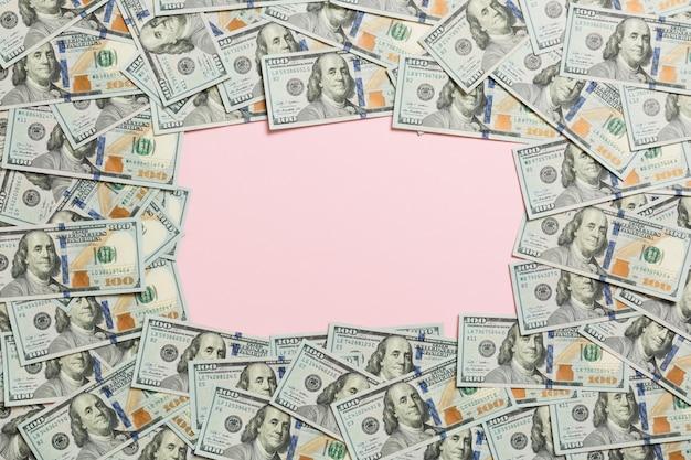 Rahmen aus dollar mit exemplar in der mitte. draufsicht des geschäfts auf rosa hintergrund mit kopienraum