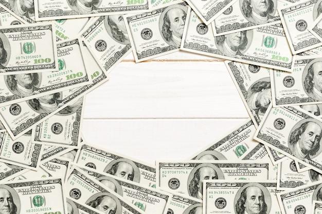 Rahmen aus dollar mit kopierplatz in der mitte. draufsicht des geschäftskonzepts auf weißem hölzernem hintergrund mit kopienraum
