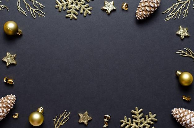 Rahmen aus festlichen weihnachtselementen auf schwarzem hintergrund. raumzusammensetzung kopieren. ansicht von oben. vorlage für eine weihnachtskarte