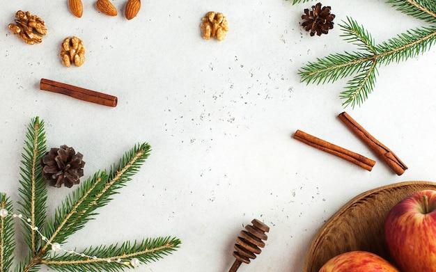 Rahmen aus fichtenzweigen, zimt, äpfeln und nüssen. weihnachtskarte. neujahr..