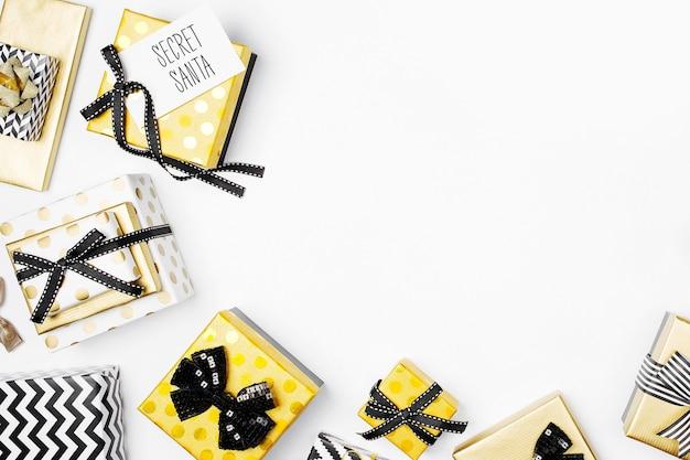 Rahmen aus flachen weihnachtsgeschenkboxen und dekorationen in den farben gold und schwarz. flache lage, ansicht von oben