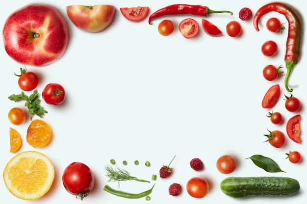 Rahmen aus gemüse und obst auf weißem hintergrund. ungewöhnlicher ort für text über kochen, ernährung, gesunde lebensweise, italienisches essen,