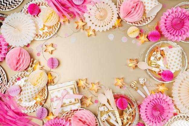 Rahmen aus goldenem und pinkfarbenem partydeko. flache lage, ansicht von oben