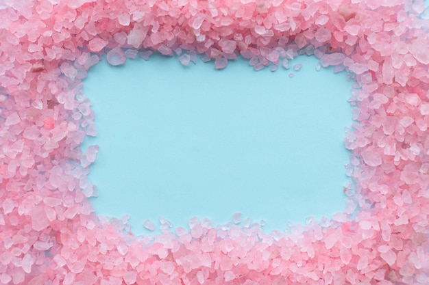 Rahmen aus groben kristallen aus rosa meersalz auf blau
