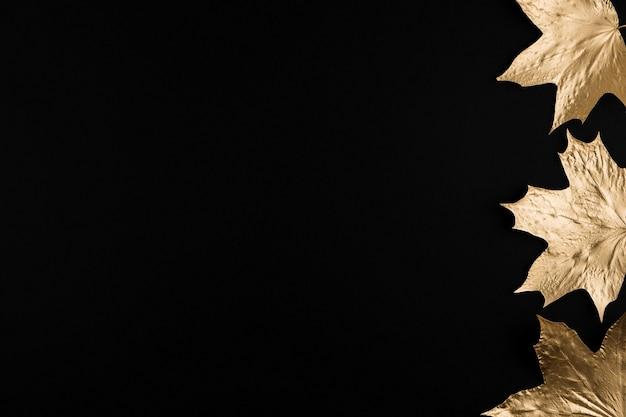 Rahmen aus herbstgoldenen ahornblättern auf schwarzem hintergrund