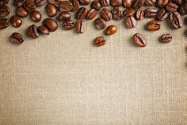 Rahmen aus kaffeebohnen auf farbiger sackleinenwand