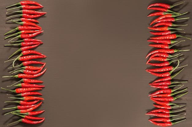 Rahmen aus kleinen glühenden chilischoten, vertikal auf braunem beton angeordnet. lebensmittelhintergrund mit kopierraum.