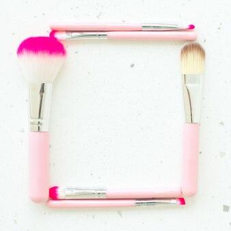 Rahmen aus make-up-pinseln auf natürlicher weißer marmorstruktur als.