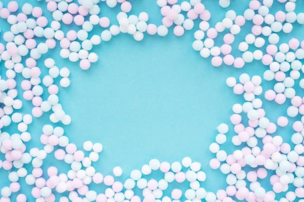 Rahmen aus mini-pompons aus pastellfarbenen kugeln auf hellblauem hintergrund mit rundem kopierraum.