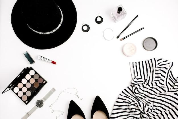 Rahmen aus moderner kleidung, accessoires und kosmetik. t-shirt, hut, schuhe, palette, lippenstift, uhren, puder auf weißem hintergrund. flache lage, ansicht von oben