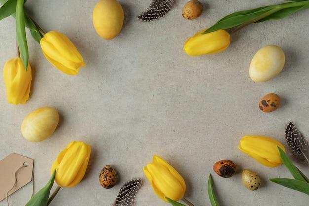 Rahmen aus natürlich gefärbten ostereiern und gelben tulpen auf grauem tisch