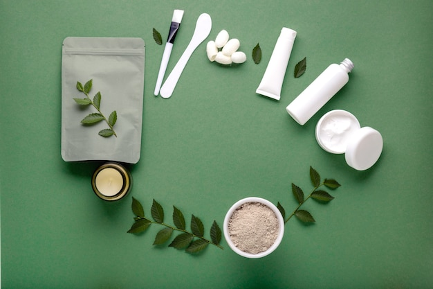 Rahmen aus naturkosmetik-sets in weißer mockup-verpackung auf grünem hintergrund. schönheit hautpflege haarbehandlung kosmetische feuchtigkeitscreme gesichtsmaske seidenraupenkokons. flach kopieren.