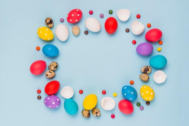 Rahmen aus ostereier und süßigkeiten auf dem tisch