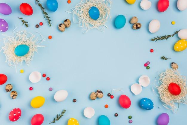 Rahmen aus ostereiern in nestern und süßigkeiten