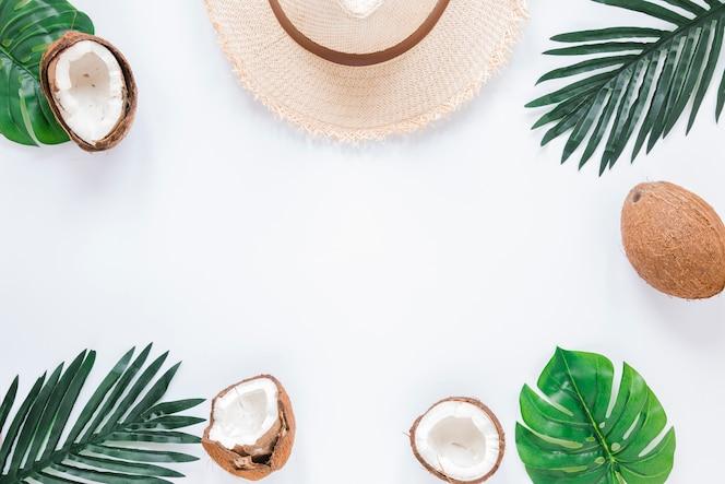 Rahmen aus palmblättern, kokosnüssen und strohhut