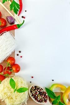 Rahmen aus reisnudeln, tomaten, paprika, basilikum, petersilie und knoblauch, weißes papier auf einem sack