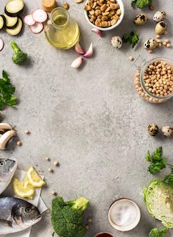Rahmen aus rohen kochzutaten für leckeres und gesundes essen. frischer fisch, gemüse, kräuter und hülsenfrüchte auf grauer hintergrundoberansicht