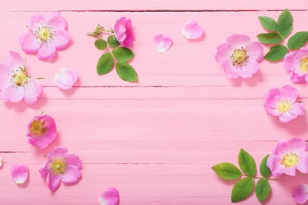 Rahmen aus rosa rosen auf rosa holz