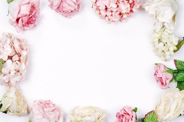 Rahmen aus rosa und beige rosen auf weißem hintergrund. flach legen