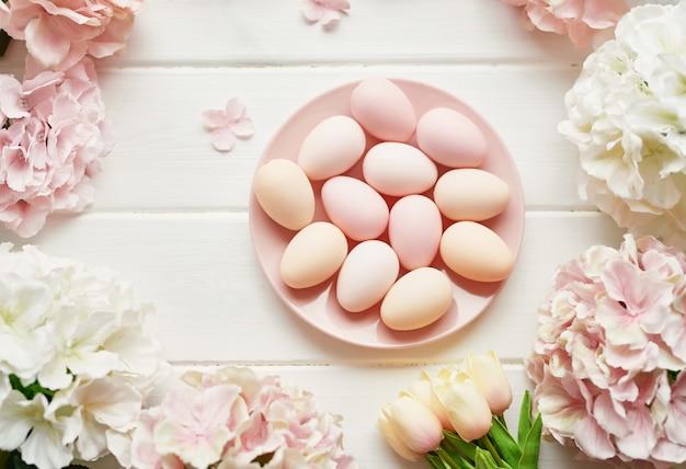 Rahmen aus rosa und beigen hortensienblüten, rosa eiern und gelben tulpen
