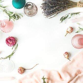 Rahmen aus rosen, lavendel, grünen eukalyptuszweigen, kerzen, leuchtern, rosa kleid