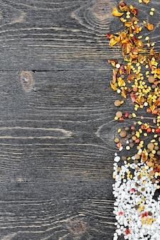 Rahmen aus salz, bockshornkleesamen, erbsen und paprikaflocken auf einem hintergrund aus schwarzen holzbrettern