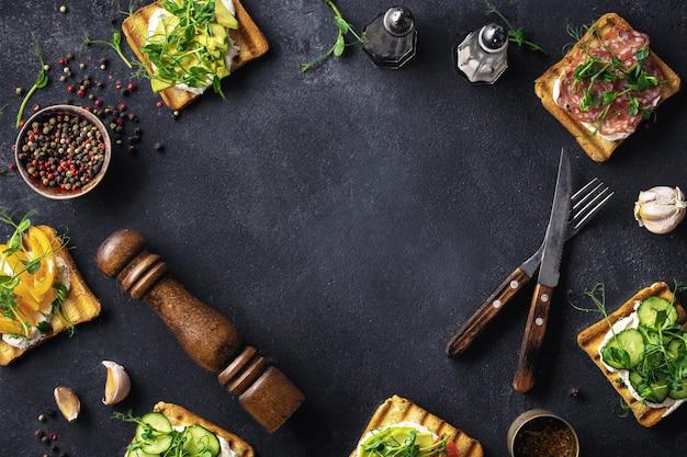 Rahmen aus sandwiches mit avocado, salami und gurke
